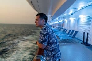 East Indian Passenger looks out from ocean liner over railing